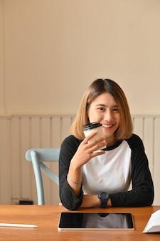 Jeune femme séduisante tenant la tasse à café et en regardant la caméra sur la table créative.
