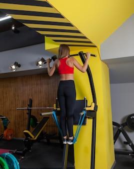 Jeune femme séduisante en vêtements de sport pratique des tractions dans une machine d'exercice dans une salle de sport moderne