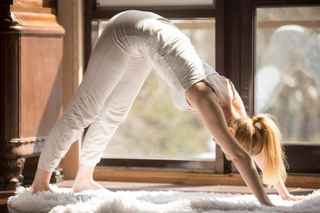 Jeune femme séduisante yogi en posture adho mukha svanasana