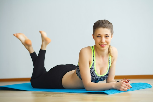 Jeune femme séduisante yogi, pratiquant le concept de yoga, portant des vêtements de sport, débardeur noir et pantalon, pleine longueur