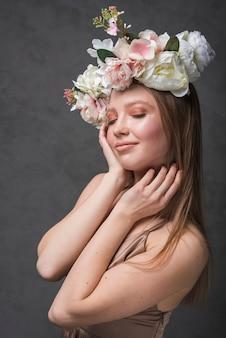Jeune femme sensuelle gaie en robe avec une couronne de belle fleur
