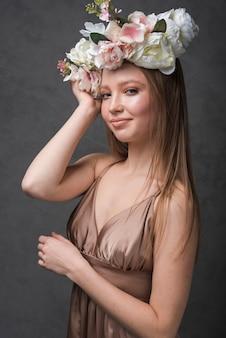 Jeune femme sensuelle joyeuse en robe avec une couronne de belle fleur