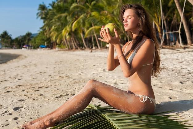 Jeune femme sensuelle en maillot de bain bikini blanc tenant la noix de coco, souriant, se faire bronzer sur la plage tropicale.