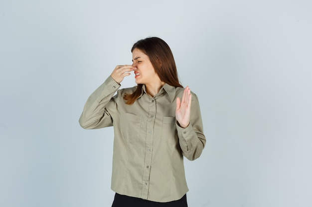 Jeune femme sentant quelque chose d'affreux, pinçant le nez, montrant un panneau d'arrêt en chemise, jupe et ayant l'air dégoûté, vue de face.