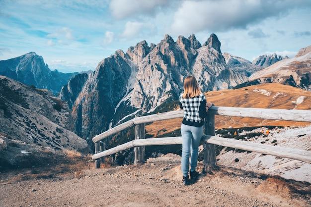 Jeune femme sur le sentier regarde sur les montagnes majestueuses au coucher du soleil en automne