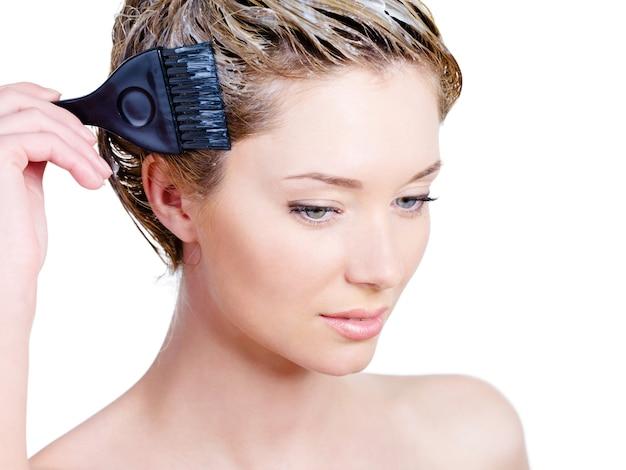 Jeune femme sereine colorant ses cheveux avec une brosse