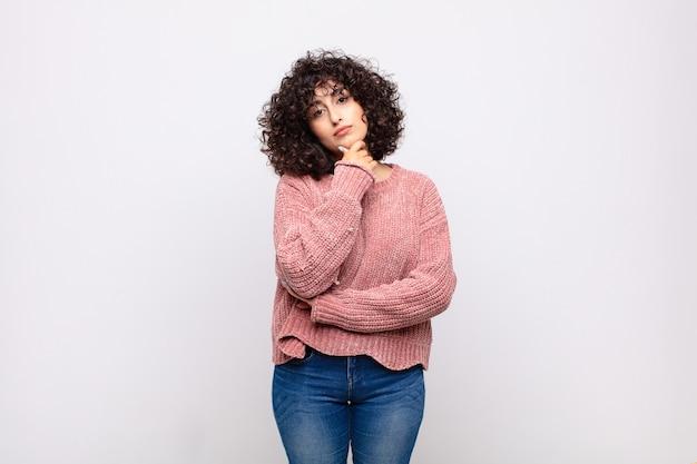 Jeune femme sérieuse aux cheveux bouclés et pull rose