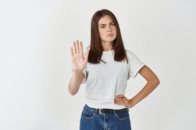 Jeune femme sérieuse disant non, étendant la paume dans le panneau d'arrêt et fronçant les sourcils déçue, refusant ou interdisant quelque chose, debout sur un mur blanc