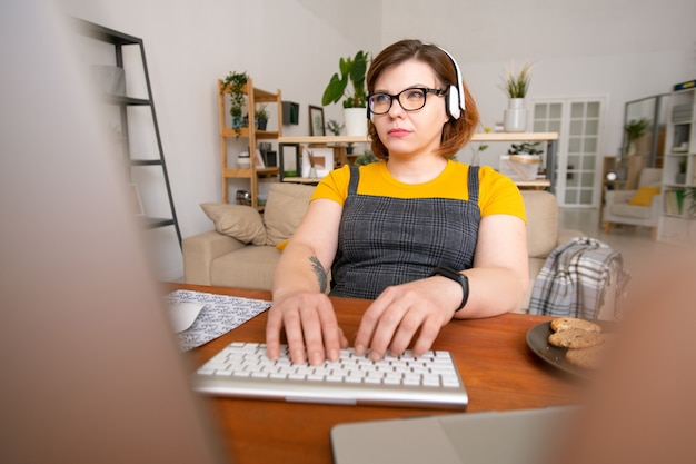 Jeune femme sérieuse avec des écouteurs en gardant ses doigts sur le clavier et en regardant les données sur l'écran de l'ordinateur tout en travaillant à la maison