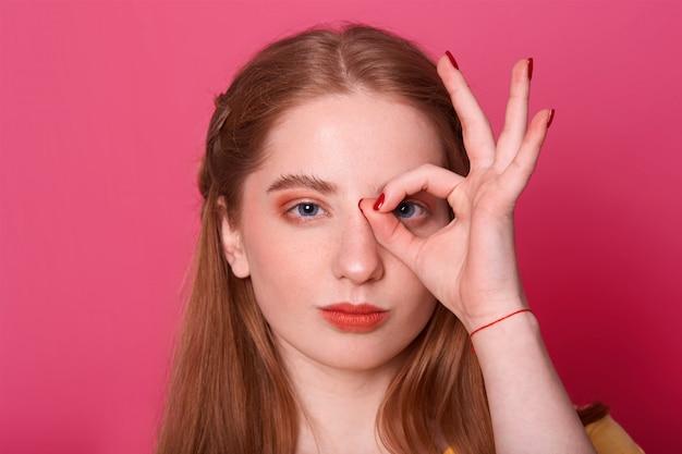Jeune femme sérieuse, fait signe ok, contre son oeil, exprime sa confiance, mannequin pose sur rose, en train de photographier. concept de personnes et de geste.