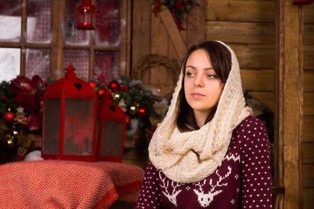 Jeune femme sérieuse avec un foulard sur la tête, posant à la maison en bois près des décorations de noël tout en regardant le cadre gauche.