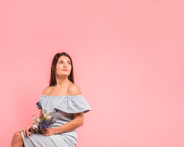 Jeune femme sérieuse tenant un bouquet de fleurs