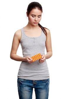 Jeune femme sérieuse tenant des médicaments dans les mains