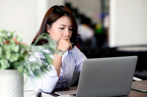 Jeune femme sérieuse travaillant avec un ordinateur portable au bureau.