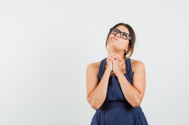 Jeune femme serrant les mains dans un geste de prière en robe et à l'espoir