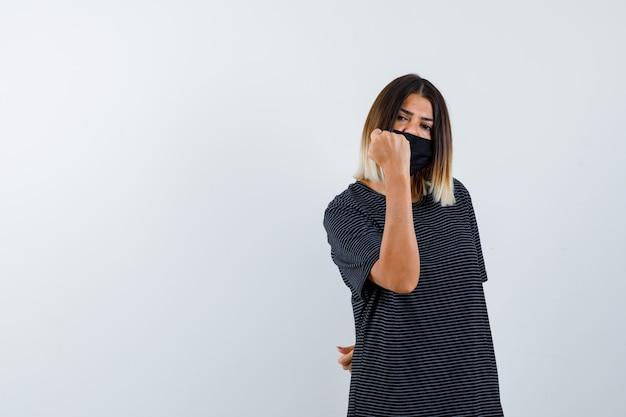 Jeune femme serrant le poing en robe noire, masque noir et à la recherche de puissance. vue de face.