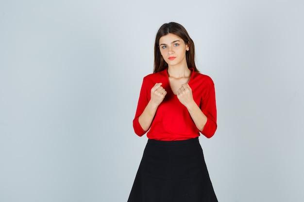 Jeune femme serrant les poings en chemisier rouge, jupe noire et à la confiance