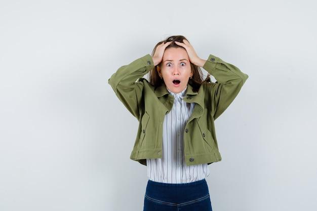 Jeune femme serrant la tête dans les mains en chemise, veste et semblant anxieuse, vue de face.