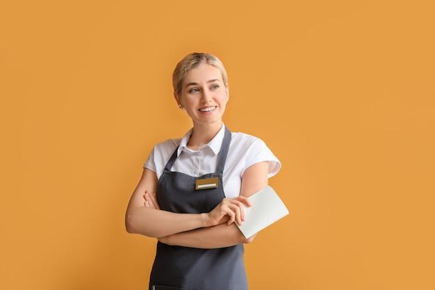 Jeune femme serveur avec badge vierge sur fond de couleur