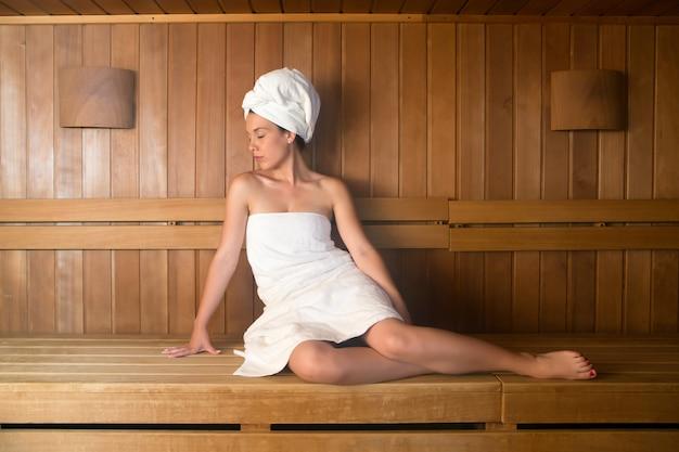 Jeune, femme, serviette, délassant, banc, sauna