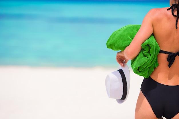 Jeune femme avec une serviette de plage verte pendant des vacances tropicales