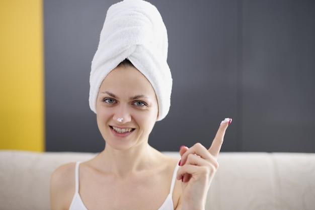 Jeune femme avec une serviette sur ses cheveux appliquant une crème protectrice sur le visage. concept de soins de la peau du visage anti-âge.