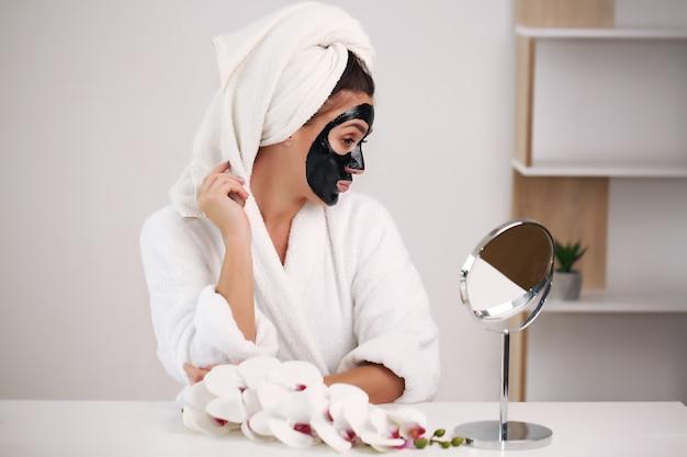 Jeune femme avec une serviette sur la tête et un masque noir assis à la maison