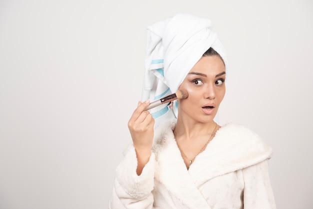 Jeune femme avec une serviette sur la tête et un pompon
