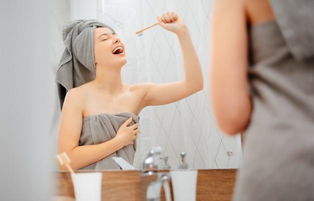 Une jeune femme avec une serviette sur la tête se brosse les dents et chante comme si la brosse à dents était un microphone. concept de dentisterie et de soins.