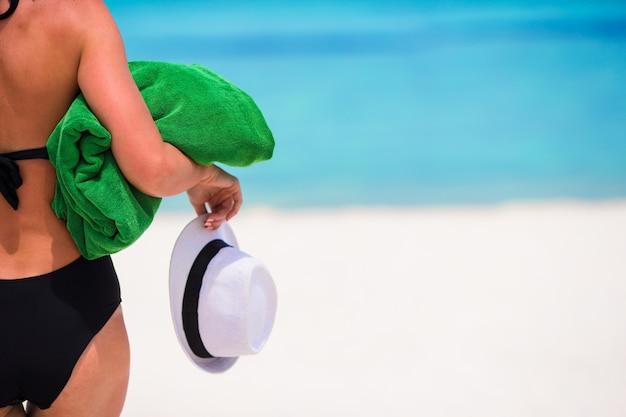 Jeune femme avec une serviette verte et un chapeau sur la plage blanche