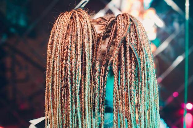 Une jeune femme, ses cheveux tressés en nattes fines bleues.