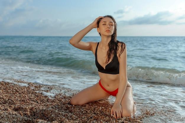 Jeune femme sexy assise sur ses genoux sur la plage