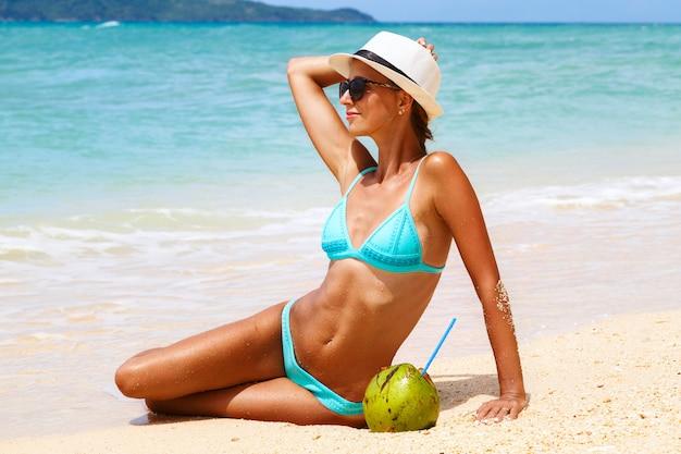 Jeune femme sexy attrayante en vacances assis sur la plage de sable fin au bord de mer