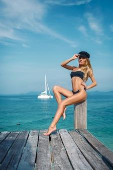 Jeune femme sexy en bikini noir et chapeau noir posant sur la jetée en bois