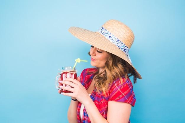 Jeune femme sexy buvant un smoothie savoureux sur fond bleu et espace de copie, tenue vintage, portrait de style de vie en studio, dessert