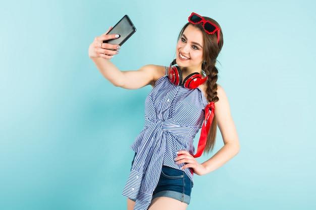 Jeune femme sexy avec un casque et un téléphone portable