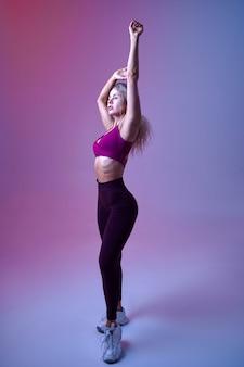Jeune femme sexy avec un corps mince pose en studio, fond néon. sportive à la séance photo, concept sportif, mode de vie actif