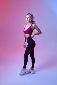 Jeune femme sexy avec un corps mince pose en studio, fond néon. sportive à la séance photo, concept sportif, motivation de style de vie actif