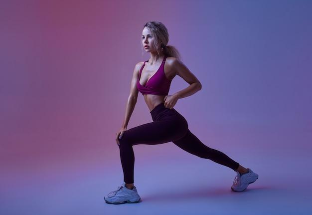 Jeune femme sexy avec un corps parfait pose en studio, fond néon