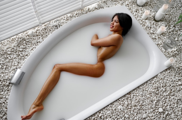 Jeune femme sexy, détente dans le bain avec du lait. personne de sexe féminin dans la baignoire, soins de beauté et de santé au spa, traitement de bien-être dans la salle de bain, cailloux et bougies sur fond