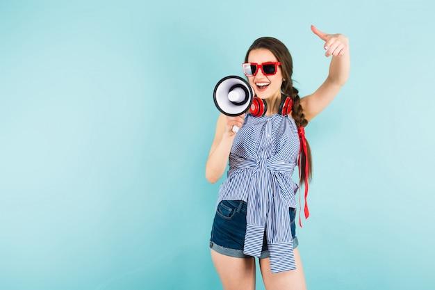Jeune femme sexy avec des écouteurs et haut-parleur