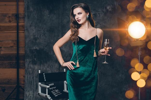 Jeune femme sexy élégante sur les coulisses du cinéma, célébrant avec une coupe de champagne