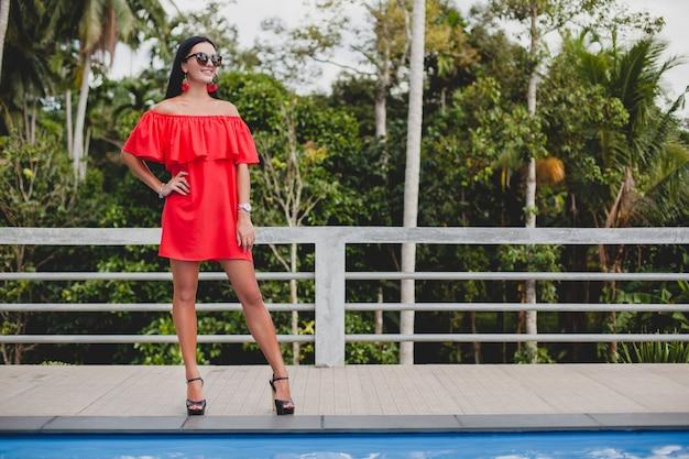 Jeune femme sexy élégante en robe d'été rouge debout sur la terrasse dans un hôtel tropical, fond de palmiers, longs cheveux noirs, lunettes de soleil, boucles d'oreilles ethniques, lunettes de soleil, impatient, chaussures à talons hauts