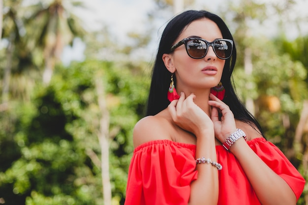 Jeune femme sexy élégante en robe d'été rouge debout sur la terrasse dans un hôtel tropical, fond de palmiers, longs cheveux noirs, lunettes de soleil, boucles d'oreilles ethniques, lunettes de soleil, impatient, gros plan