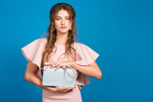 Jeune femme sexy élégante en robe de luxe rose, tendance de la mode estivale, style chic, fond de studio bleu, tenant le sac à main à la mode