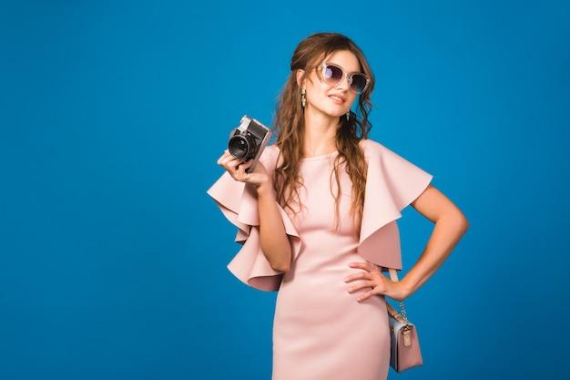 Jeune femme sexy élégante en robe de luxe rose, tendance de la mode estivale, style chic, lunettes de soleil, prendre des photos sur appareil photo vintage