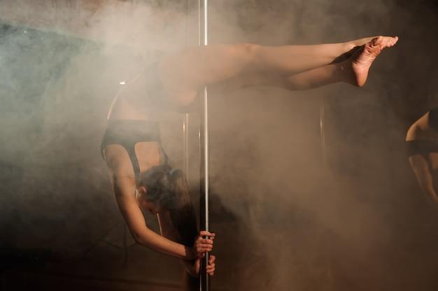 Jeune femme sexy exercice pole dance. aptitude