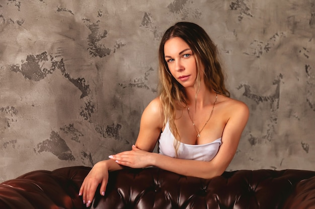 Jeune femme sexy expressive blonde vêtue d'un t-shirt mouillé blanc et d'un jean posant sur un fond sombre texturé. les seins s'égouttent gouttes d'eau. fille séduisante d'émotion de corps dans des vêtements décontractés humides. espace de copie