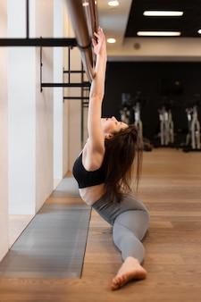 Jeune femme sexy faisant des exercices d'étirement dans une salle de sport
