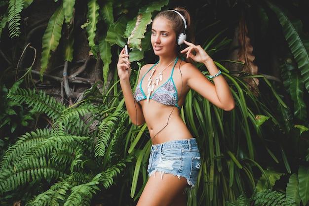 Jeune femme sexy en haut de bikini et short en jean, écouter de la musique sur des écouteurs, tenant un smartphone, peau bronzée, corps maigre, fond tropical vert, danse, souriant